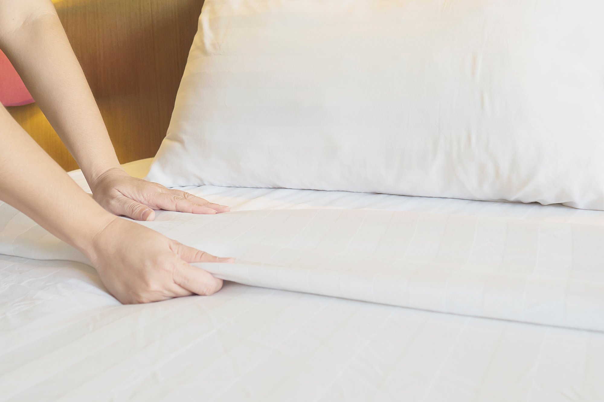 lady-hands-set-up-white-bed-sheet-in-hotel-room